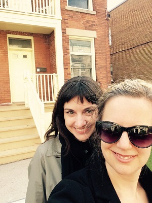 Keri Ryan and Leanne Dufault stand together, smiling, in front of a semi-detached house.