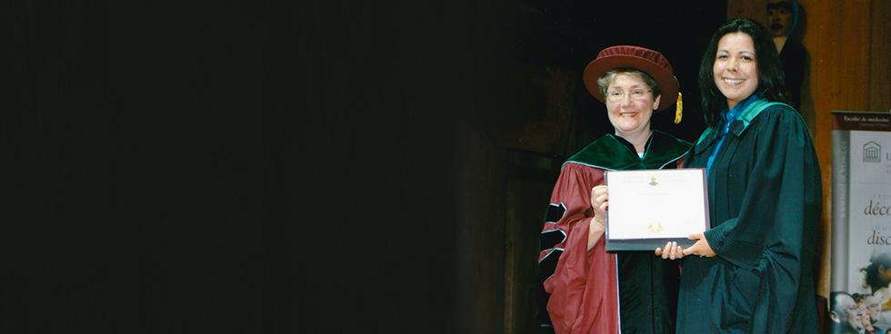 Mary Senterman et Kona Williams vêtues d'une toge tiennent ensemble un diplôme lors de la collation des grades.