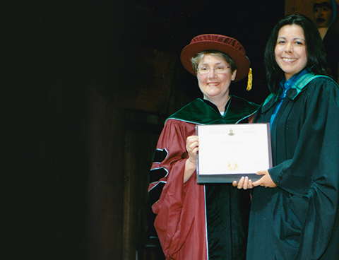 Dr. Mary Senterman and Kona Williams, wearing graduation gowns, stand together holding a medical diploma at a convocation ceremony.