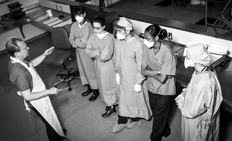 Black and white image of five medical students wearing gowns and surgical masks listening to a professor, who is wearing a white apron, in a pathology lab.