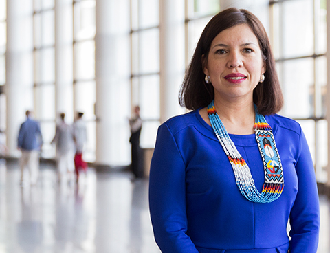 Anita Tenasco, standing in a museum lobby, wearing a colourful First Nations beaded necklace