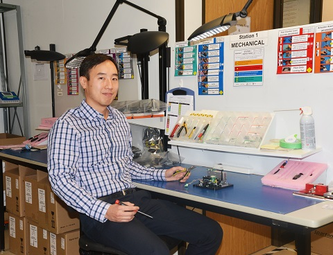 Dr. Paul Lem sits at a work bench with a screwdriver and pliers in his hands and a prototype machine on the table.