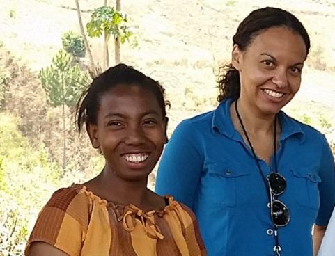 Lidia Kayembe et une jeaune fille debout à l'extérieur, dans un milieu rural.