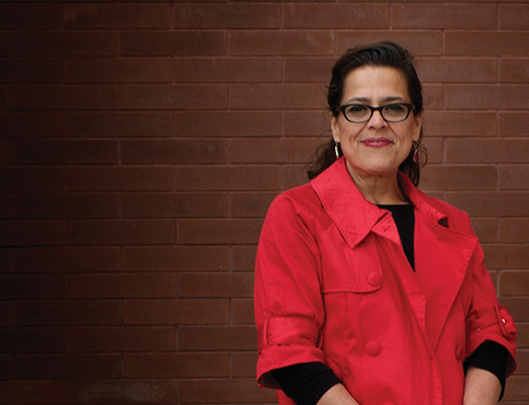 Tracey Lindberg, wearing a red shirt, black glasses and silver earrings, faces the camera, smiling.