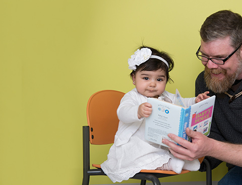 A man and a baby look at a children's book.