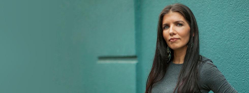 Lisa Monchalin, debout devant un mur de brique, porte des boucles d'oreilles aux motifs amérindiens.
