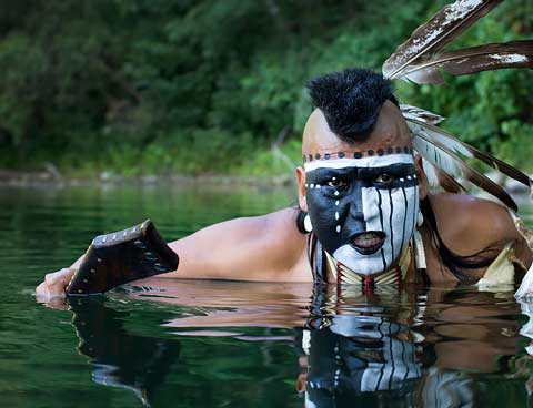 A man with his face painted emerges from the surface of water.
