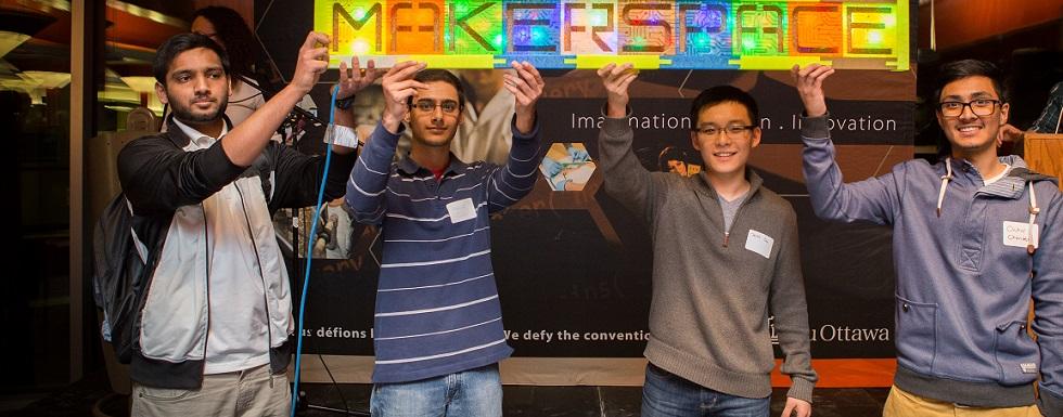 Quatre étudiants portent une pancarte avec le logo de MakerSpace.