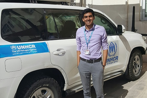 Malik Ladhani stands beside a car emblazoned with the UNHCR logo.