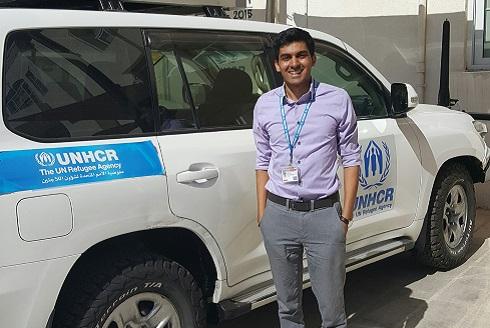 Malik Ladhani se tient devant un véhicule du HCR.