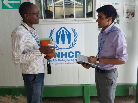 Two men face each other, with the UNHCR logo in the background.