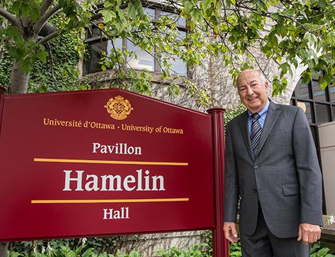 Former uOttawa President Marcel Hamelin stands to the left of a sign that reads 'Hamelin Hall'.