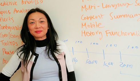 Mina Lux stands in front of white board with the words 'multi-language', 'content', 'mobile' and 'history function' written on it.