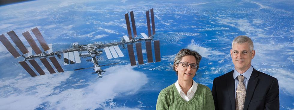 Un homme et une femme devant un écran montrant une photo de la Station spatiale internationale et de la Terre prise de l'espace.