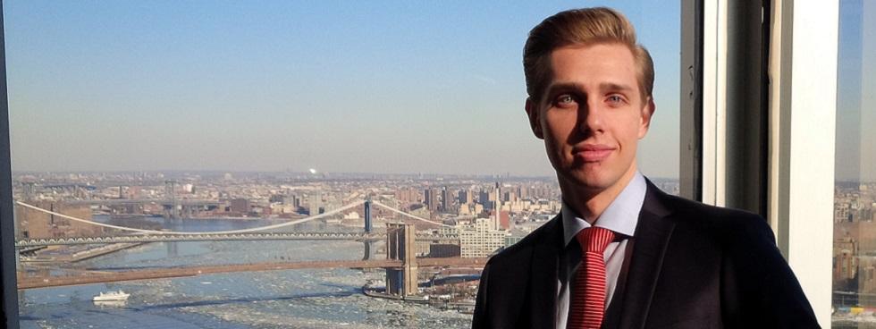 Jean-Christophe Martel stands in front of an office window overlooking the Brooklyn Bridge.