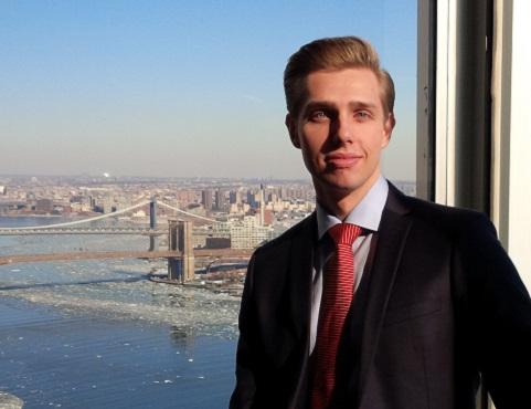 Jean-Christophe Martel debout devant une fenêtre de bureau d'où on voit le pont de Brooklyn.