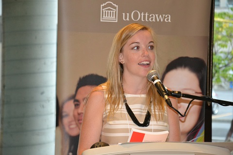Megan Cotnam-Kappel speaking at a podium with a uOttawa banner in the background.