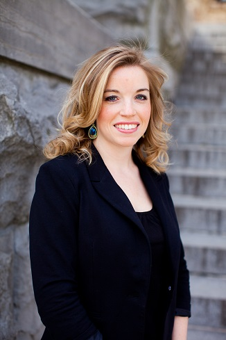 Megan Cotnam-Kappel stands outside by some grey stone steps.