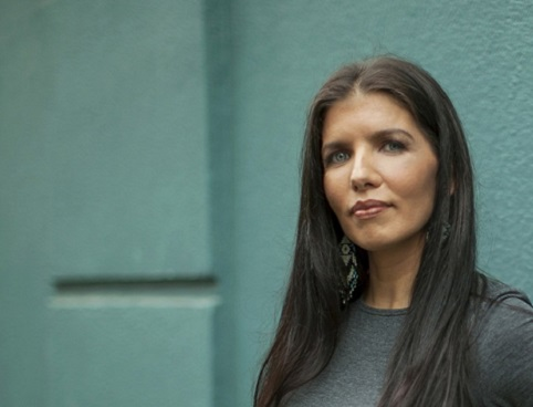 Lisa Monchalin, wearing earrings with an indigenous design, stands in front of a brick wall.
