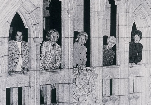 Five women framed by the arches of Centre Block on Parliament Hill.