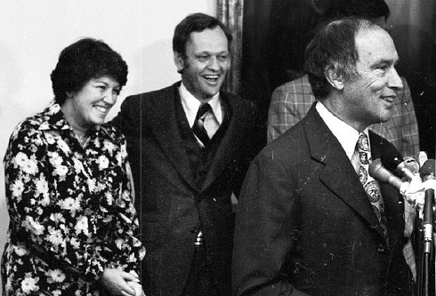 Monique Bégin and Jean Chrétien stand behind Pierre Trudeau, who is at a microphone. All three are smiling.