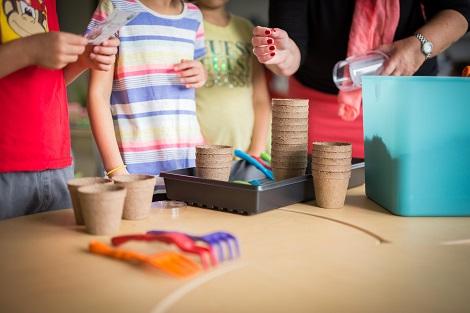 Trois enfants et Carole Payant se tiennent debout près d'une table sur laquelle on retrouve des pots de tourbe et des outils de jardinage en plastique.