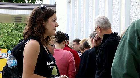 Nancy Kenny, in a T-shirt and wearing a backpack, chats with people standing in line to attend a fringe festival.