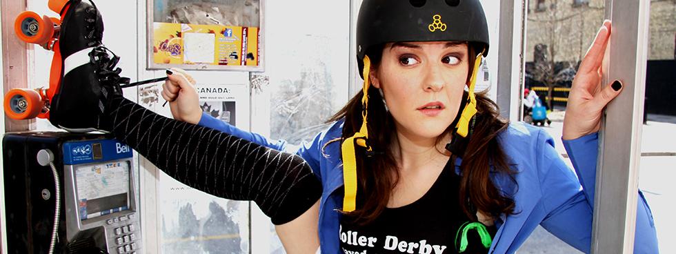 Nancy Kenny dans une cabine téléphonique, portant des patins à roulettes et un casque protecteur. Une de ses jambes est levée et appuyée sur le téléphone.