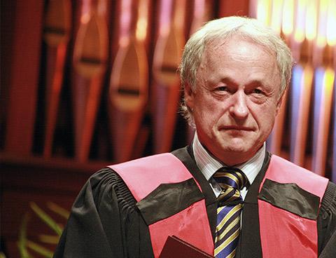 Daniel Poliquin, vêtu d'une toge noire et d'une épitoge rouge tient un diplôme dans ses mains.