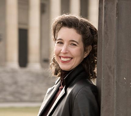 Portrait photographique d'Angela Hewitt appuyée contre une colonne de béton.