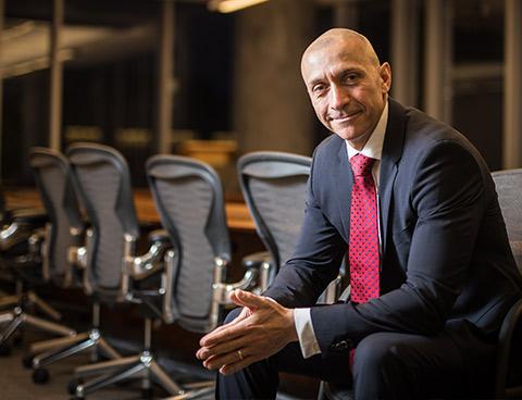 Un homme en complet est assis à une grande table de conférence, les mains jointes et penché vers l'avant.