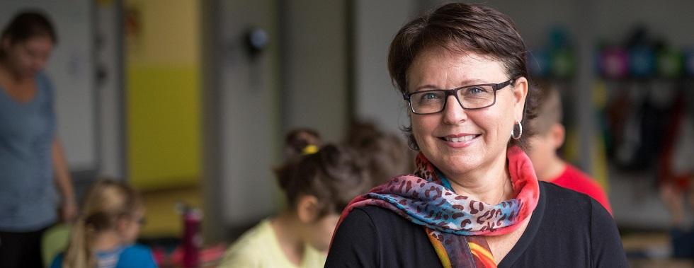 Carole Payant se tient debout dans une salle de classe. Derrière elle, des enfants font différentes activités.