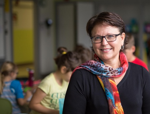 Carole Payant stands in a classroom with several children in the background.