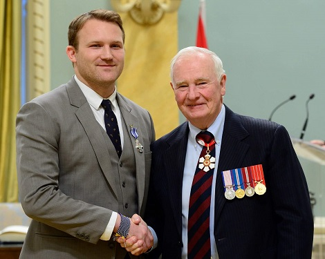 Peter Wright, an award pinned to suit lapel, shakes hands with Governor General David Johnston