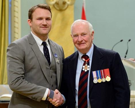 Peter Wright, arborant une médaille sur le revers de son costume, serre la main de David Johnston, gouverneur général du Canada
