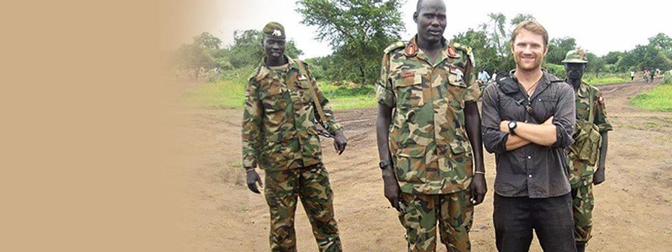 Sur un chemin de terre, Peter Wright se tient, souriant, à côté de trois soldats en tenue de combat
