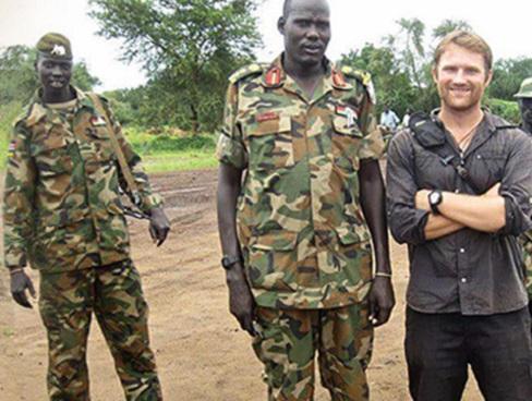 Sur un chemin de terre, Peter Wright se tient, souriant, à côté d'un soldat en tenue de combat