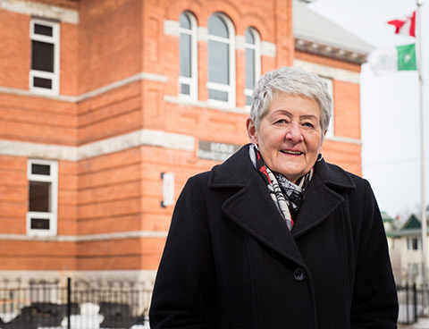 Mariette Carrier-Fraser in front of a red brick school flying the Canadian and Franco-Ontarian flags.