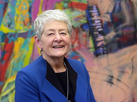 Mariette Carrier-Fraser, souriante, se tient debout devant une murale colorée.