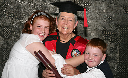 Mariette Carrier-Fraser wearing a red gown, with her two grandchildren, Zoé and Nicholas Monette.