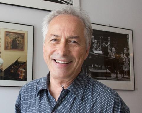 Le photographe Jean-Marc Carisse sourit à côté de ses photos accrochées au mur derrière lui.