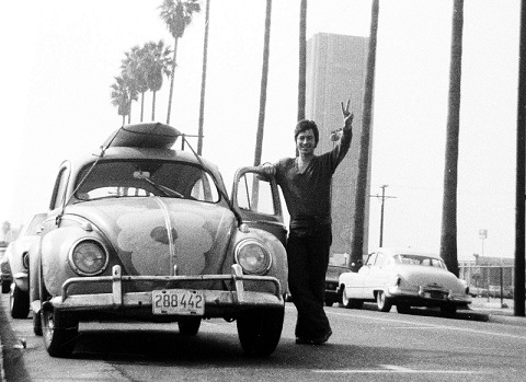 Jean-Marc Carisse près de sa coccinelle de Volkswagen faisant le signe de la paix.