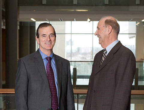 Two men in suit and tie standing, one smiling for the camera while the other looks at him, laughing.