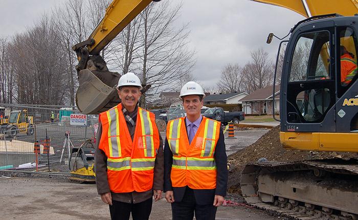 Daniel Letouzé and Marc LeBoutillier in front of a construction site.