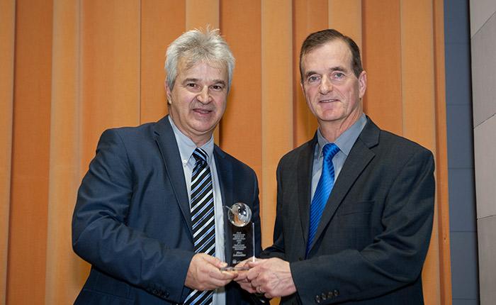 Marcel Mérette presents a trophy to Marc LeBoutillier.