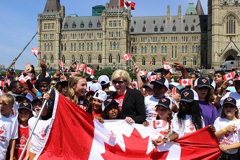 Carla Qualtrough et quelques autres personnes tiennent un grand drapeau du Canada. De nombreux étudiants tiennent des petits drapeaux et les édifices du Parlement sont à l'arrière-plan.