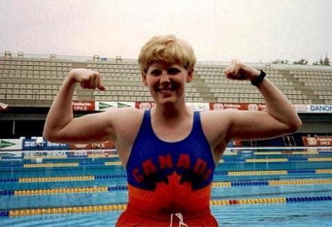 Debout près d'une piscine, Carla Qualtrough, dans un maillot portant le mot « Canada » et une feuille d'érable, gonfle les muscles de ses bras en souriant.