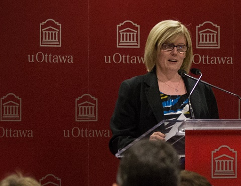 Carla Qualtrough stands behind a lectern speaking to students.