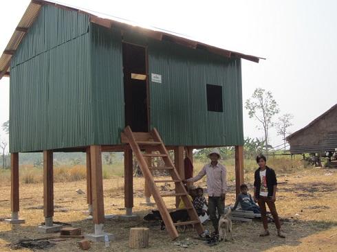 Une famille cambodgienne près d'une maison sur pilotis aux murs en feuilles de métal ondulé.