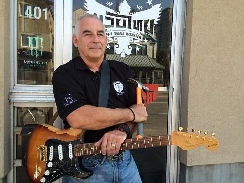 Bob Carver pose avec sa guitar Fender Stratocaster et un marteau devant une école de kickboxing Muay Thai.
